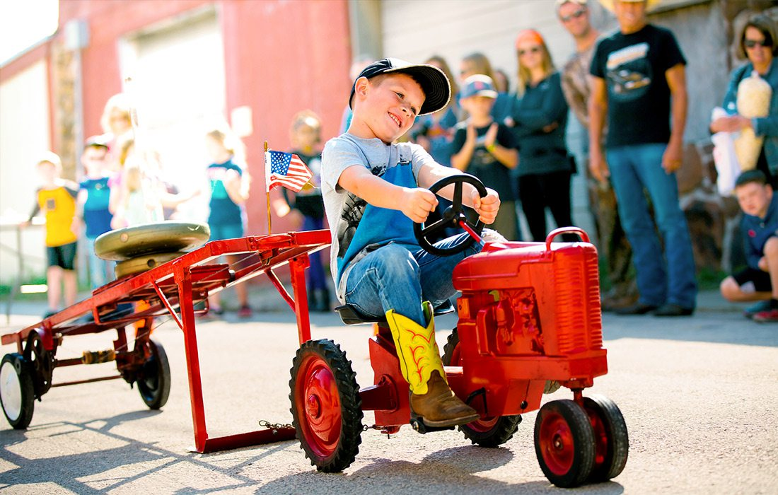 Kid on small tractor at fall festival