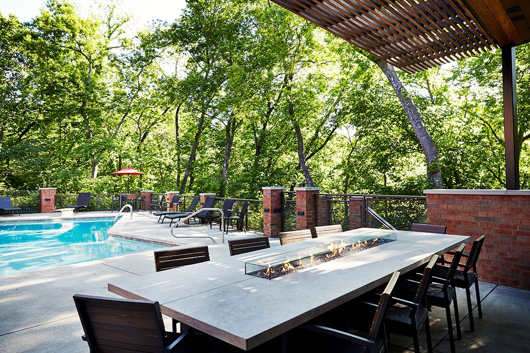 outdoor dining space by an in-ground pool
