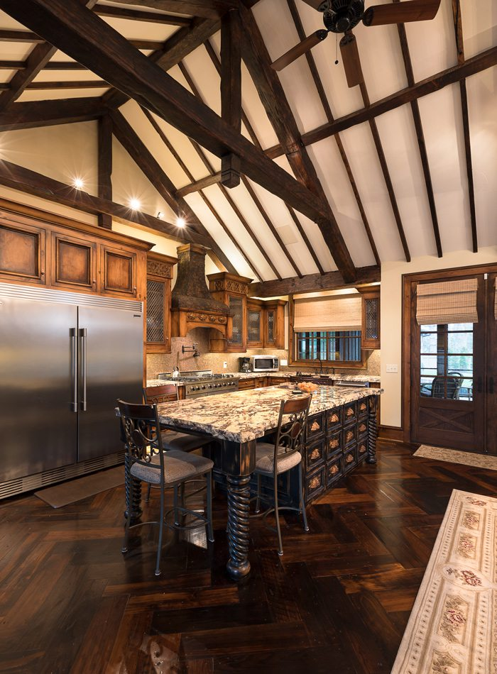 Tudor kitchen with island and vaulted wood ceilings.