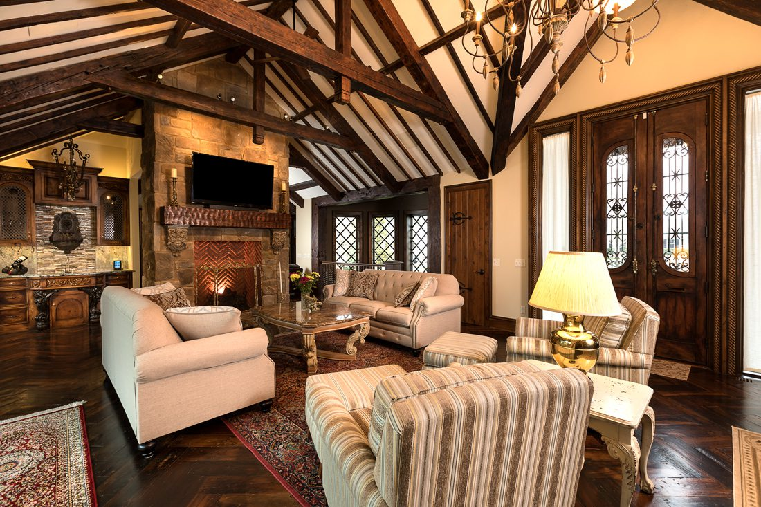 Tudor living room in Harry Potter home with wood beam ceiling, French door, chandelier.