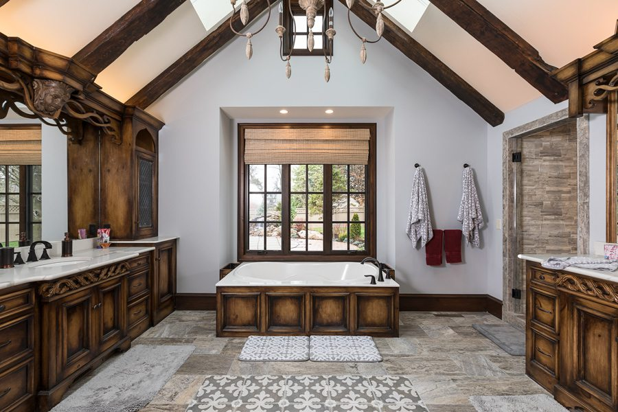 Tudor style master bath with skylights and wooden fixtures.