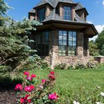 Slider Thumbnail: Tudor style home tower with windows and landscaping.