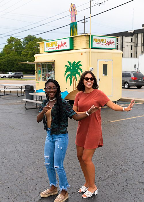 Two young girls doing the hula outside a Pineapple Whip cart in Springfield MO