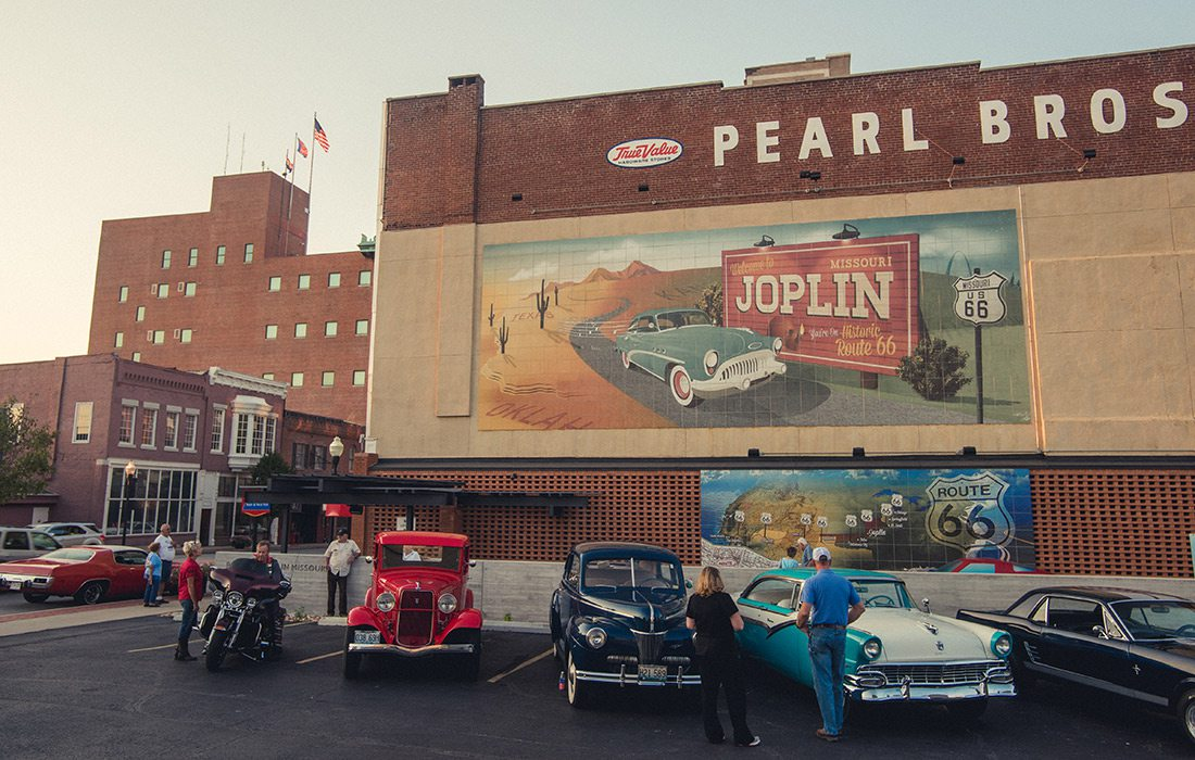 Classic cars sitting in front of the Route 66 mural in Joplin MO