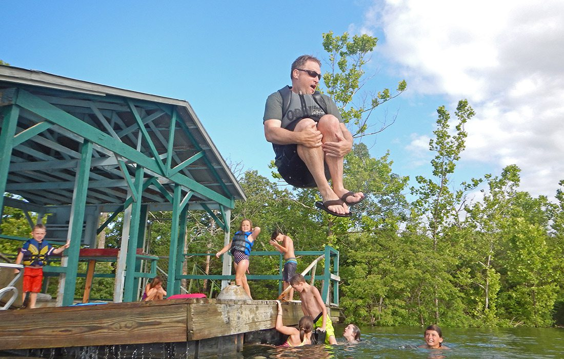 Father doing a cannon ball of the dock at Table Rock Lake in Branson MO