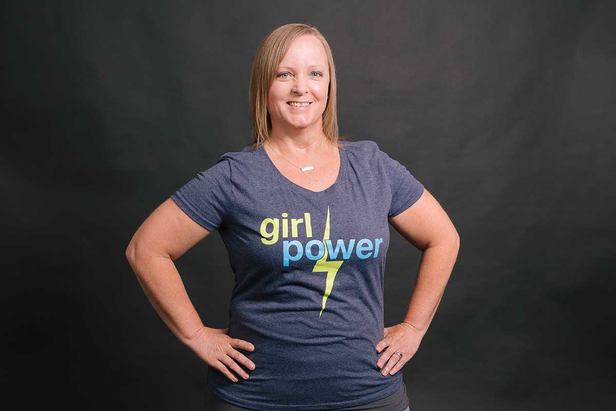 "Shana stands with her hands on her hips, smiling in her ""girl power"" t-shirt"