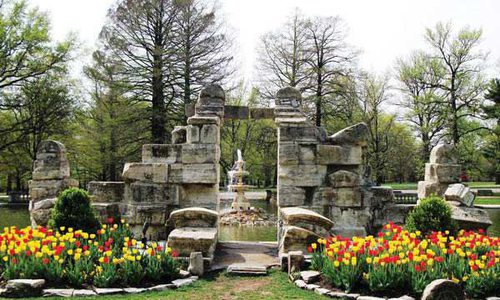 The stone gateway to Tower Grove Park blooms with tulips and the green grass surrounding