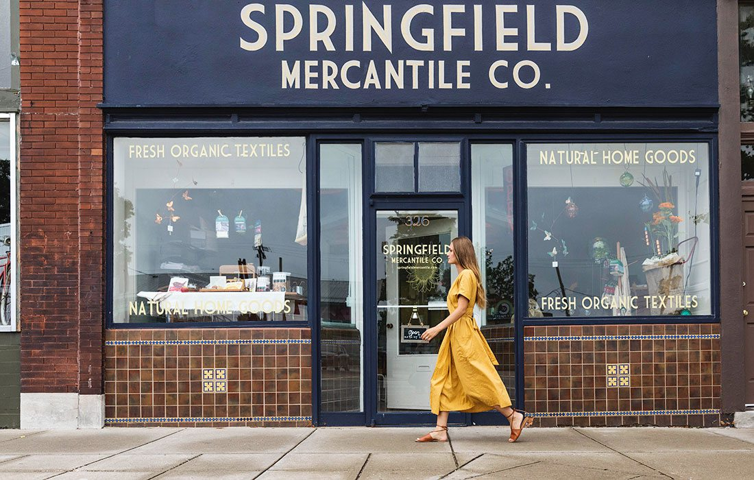 Woman in a yellow dress walking in front of springfield mercantile on commercial street in springfield mo