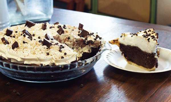 A slice of chocolate pie covered in whipped cream sits on a plate next to the rest of the pie