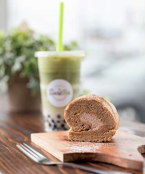 A piece of the roll up cake sits on a wooden serving dish with a bubble tea in the background