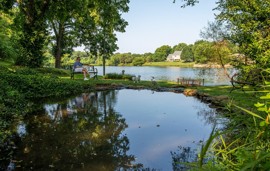 Pete Garrett sits by the picturesque spring on his yard that feeds one of the neighborhood lakes.