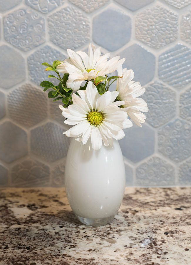 Light blue handmade tile backsplash and a white vase with white flowers