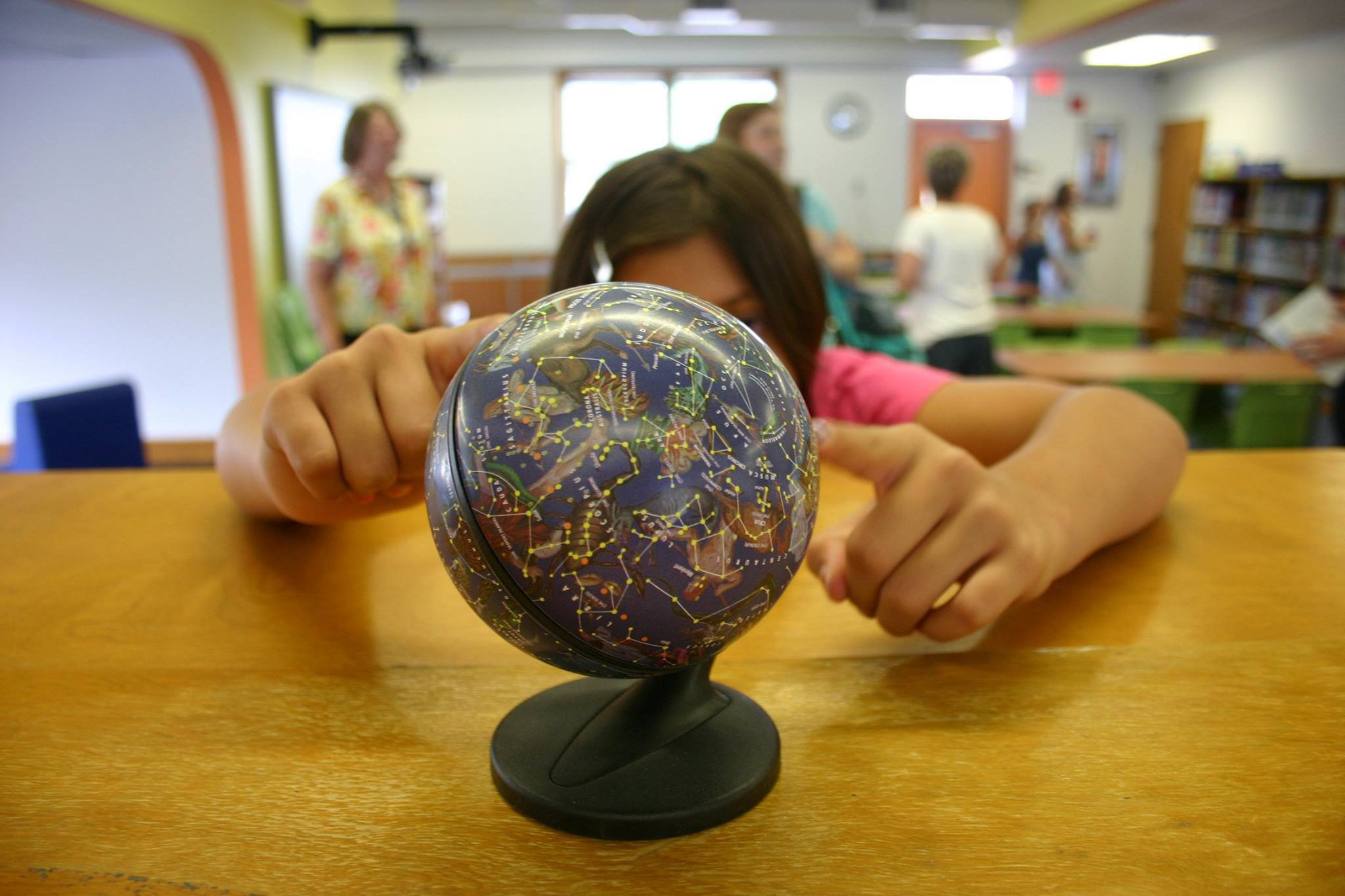 child at school looking at a globe