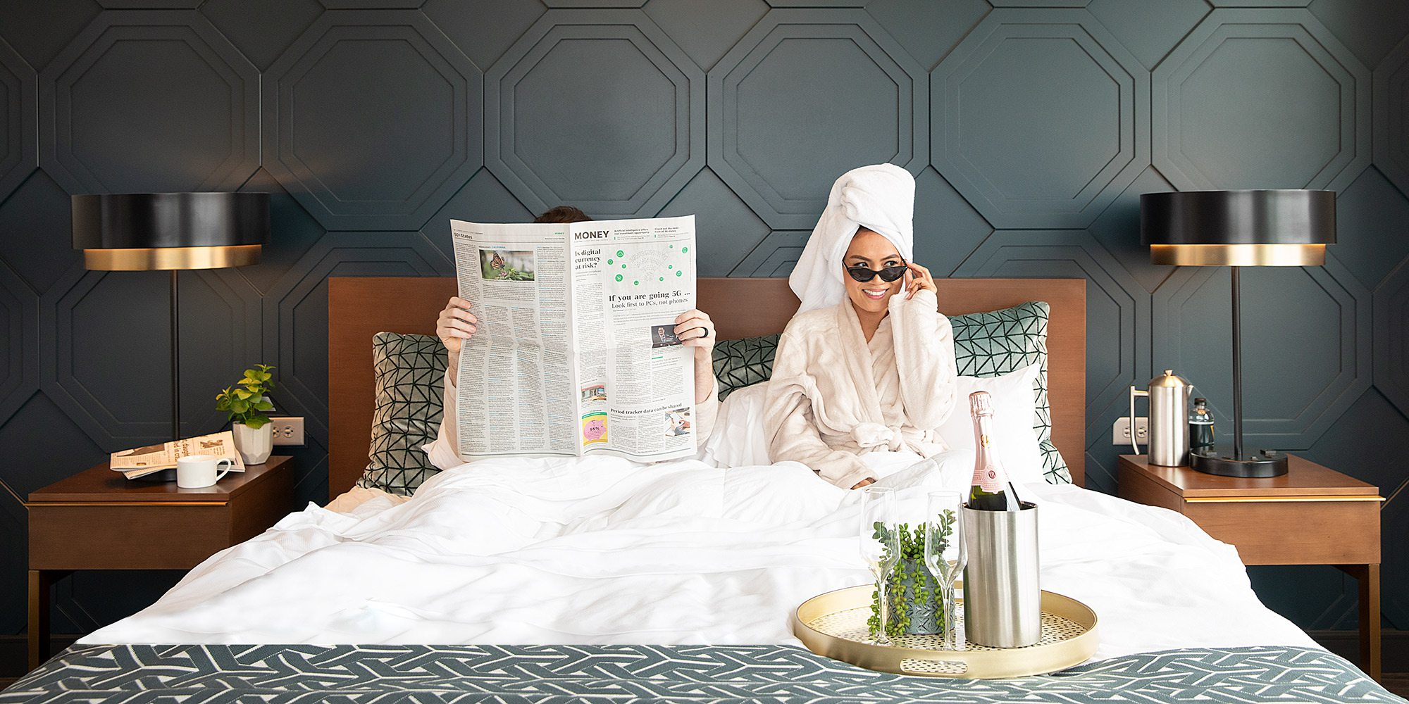 Couple lounging in bed at Hotel Vandivort in Springfield, MO