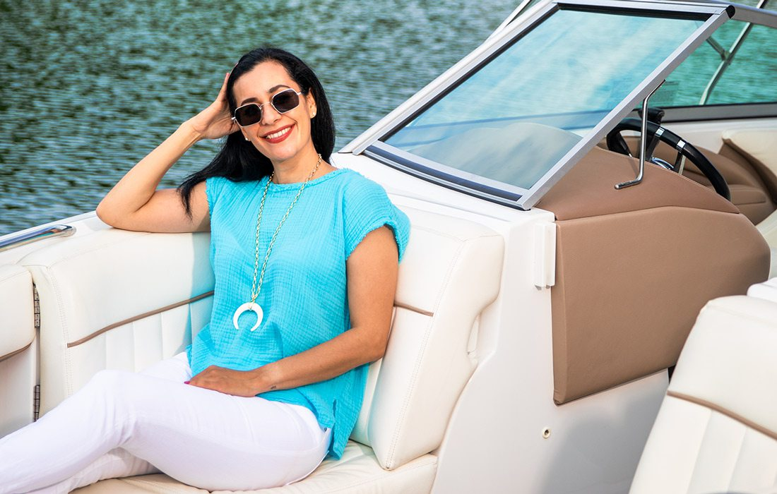 Summer style model sitting in boat on the lake