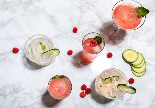 Summer cocktails with ingredients on marble counter