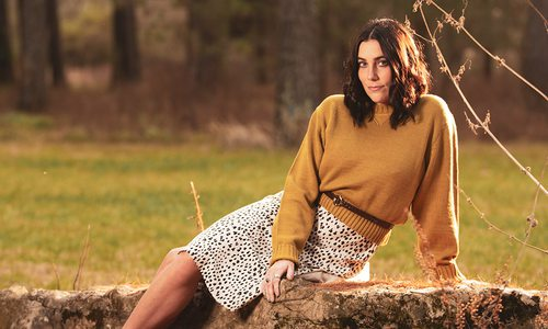 Young woman wearing a yellow sweater and animal print skirt