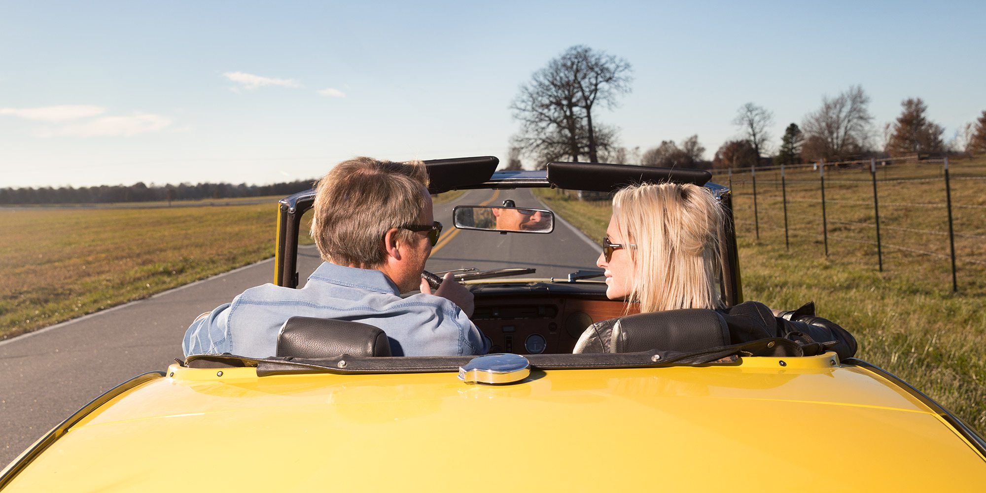 Couple hitting the road in a yellow convertible