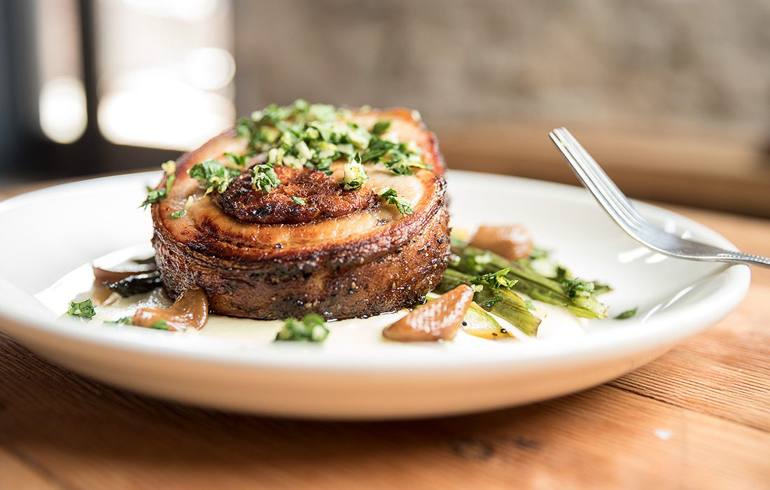 In the porchetta dish, parsnip and carrot cognac purees sit beneath a pork belly round.