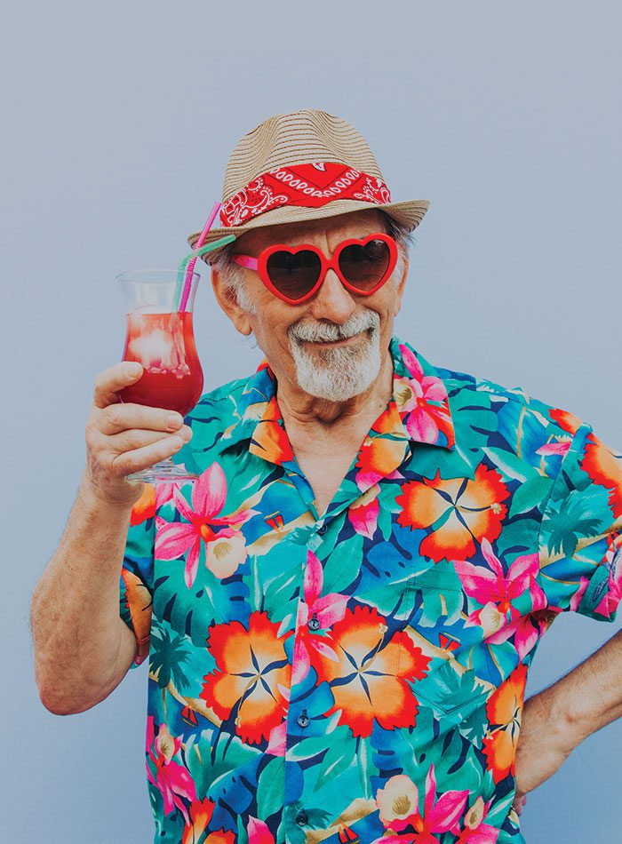 older man with drink and bright hawaiian shirt