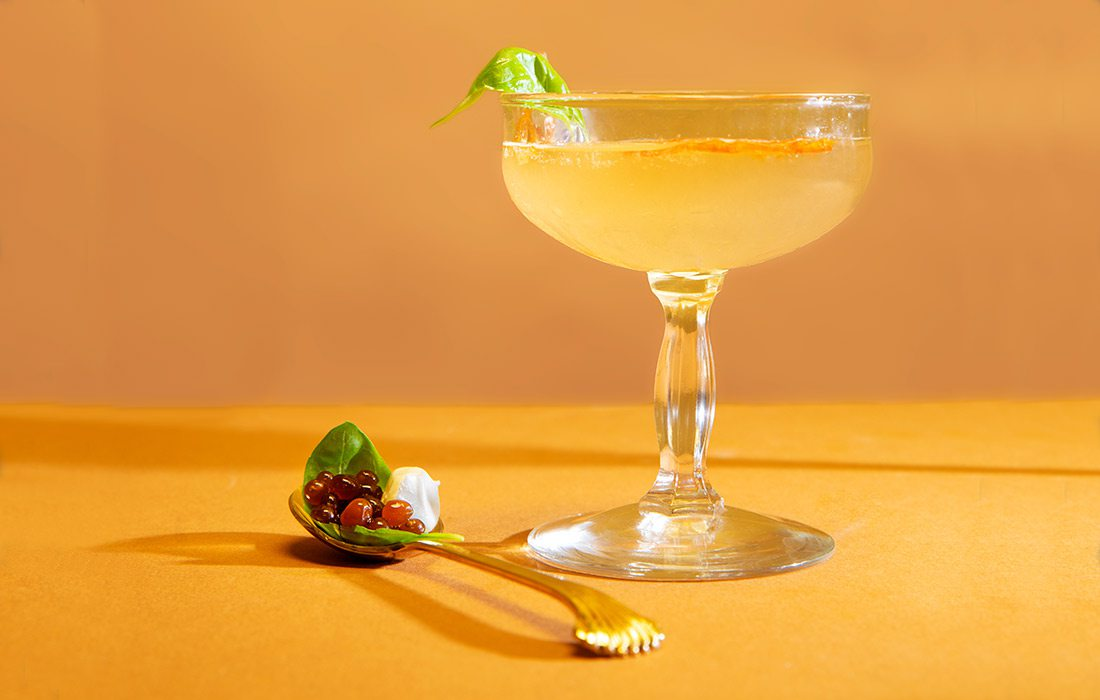 Caprese Martini with droplets on orange background.