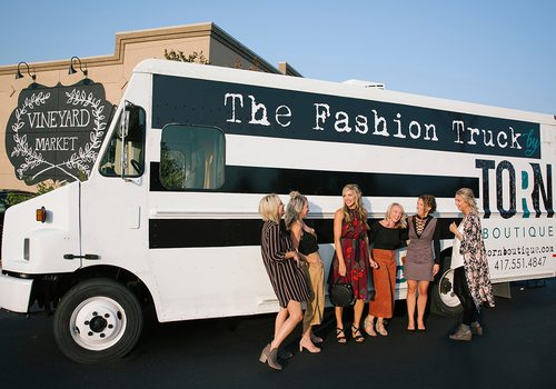 ladies laughing in front of a fashion truck