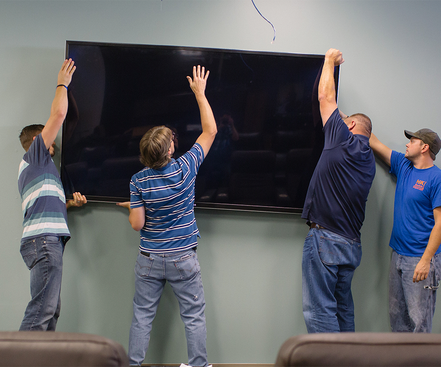 Employees Ryan Meredith, Michael Black and Michael Cory and Matthew Williams with HK Electric install an 85-inch TV at the PILR TECH office.