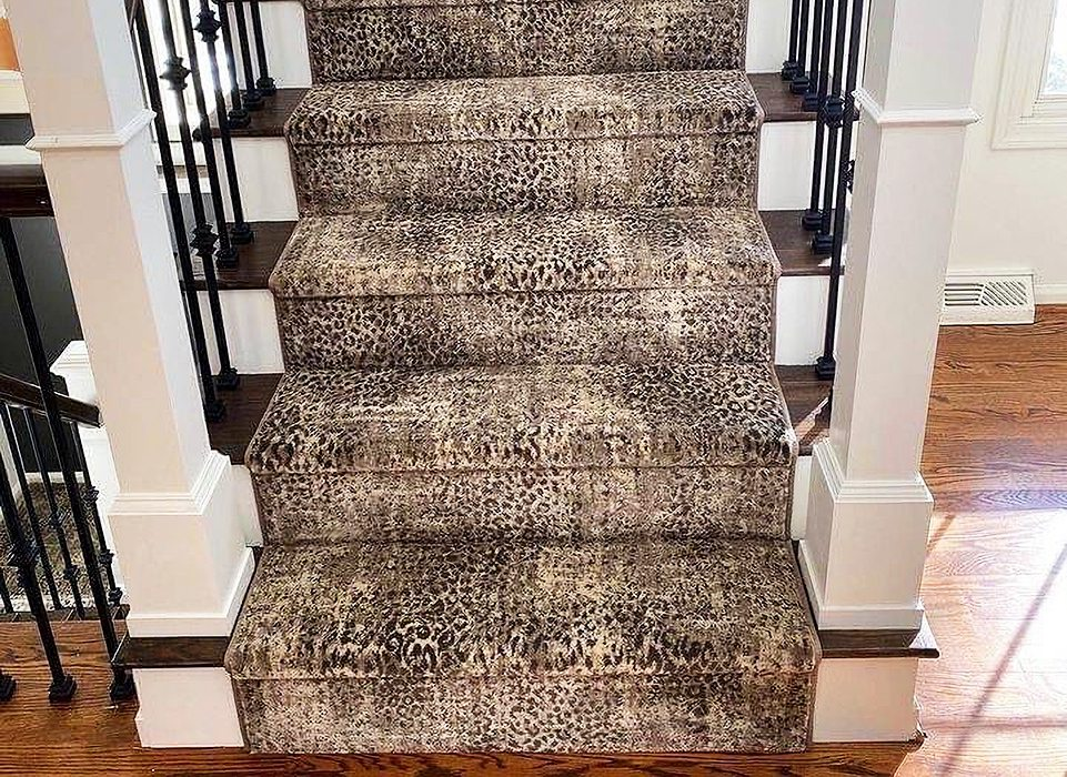 Cheetah Print rug on wooden staircase with black iron railing