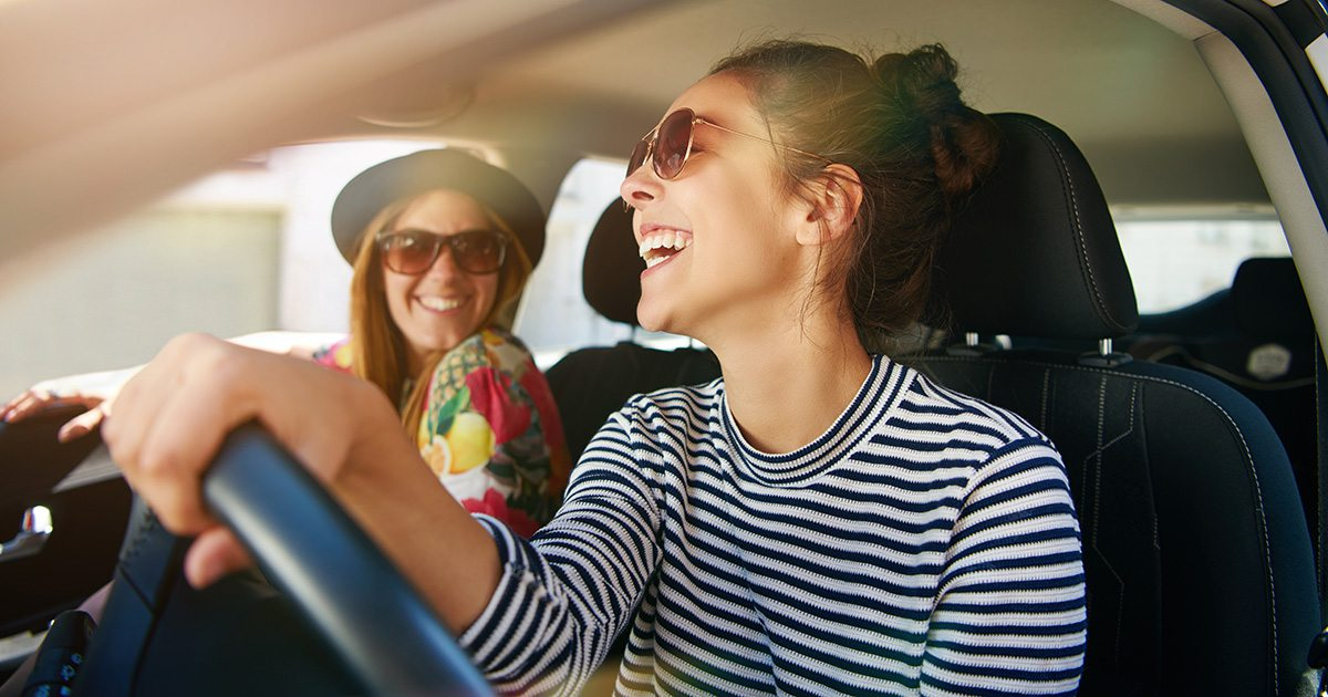 two women smiling in a car