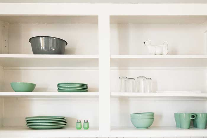 white open shelving with mint green dishes