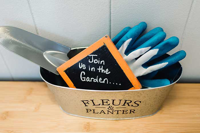 "gardening bucket with gardening gloves and sign inside reading ""Join us in the garden..."""