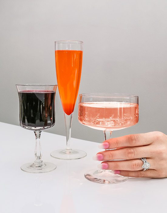 woman's manicured hand with three cocktails