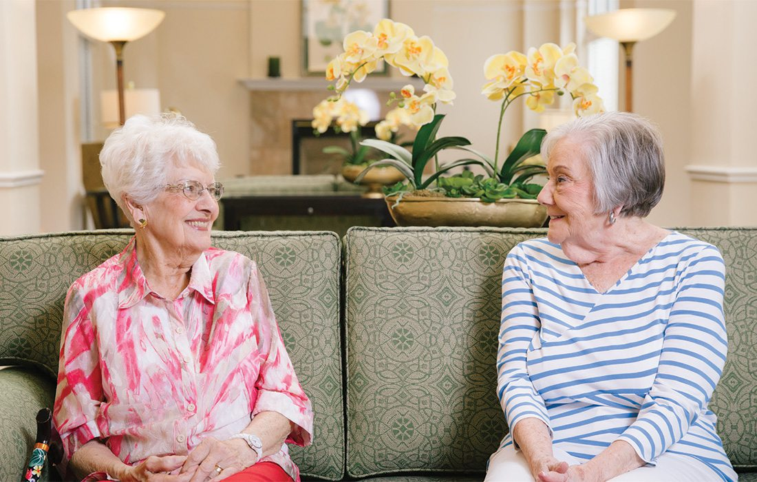 older ladies sitting on a couch talking