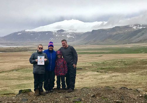 family standing in front of mountain landscape