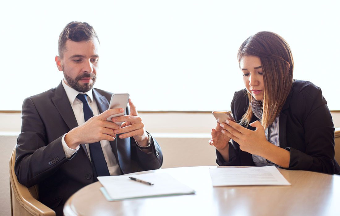 two people distracted by cell phones at work