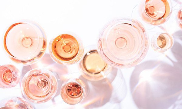 Rosé wine in glasses on a white surface
