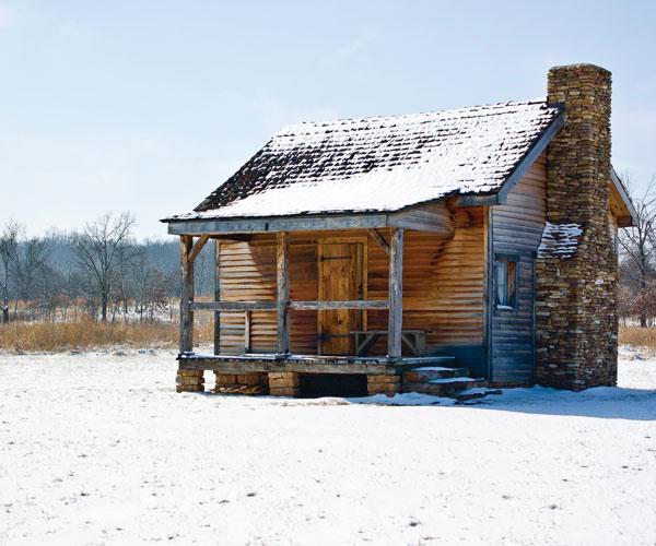 Snow-covered cabin in field during winter.