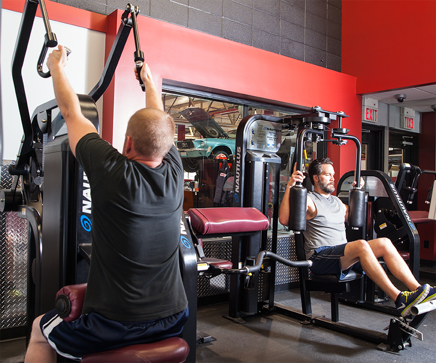 Rick's Automotive employees Dan Williams and Micah Blake squeeze in a lunch-time workout at the company's on-site gym.