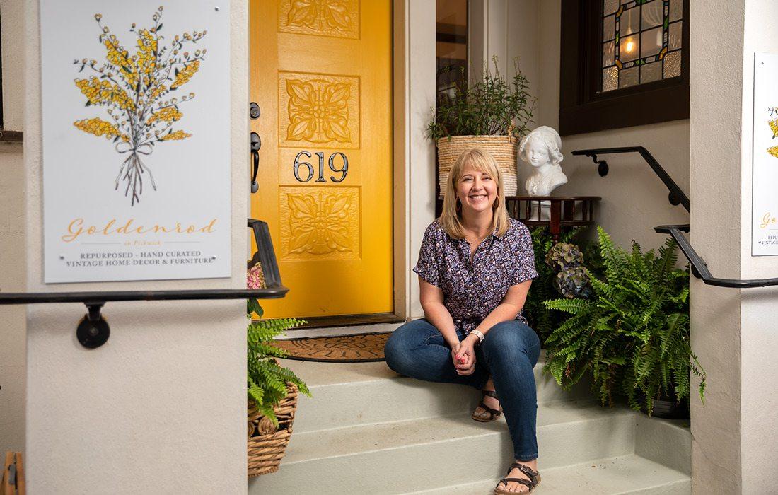Jen Jeppsen sits in front of yellow door at Goldenrod