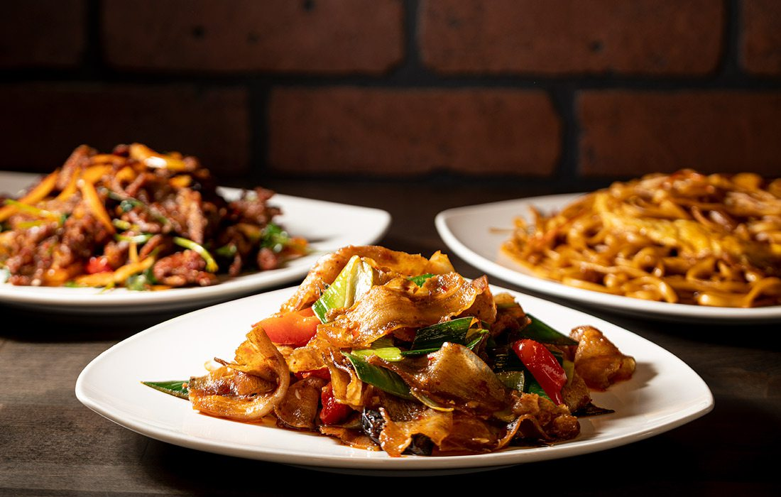 Three white plates of chinese food on wooden table