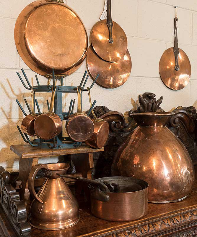 copper pots hanging from the wall and set up on wooden table