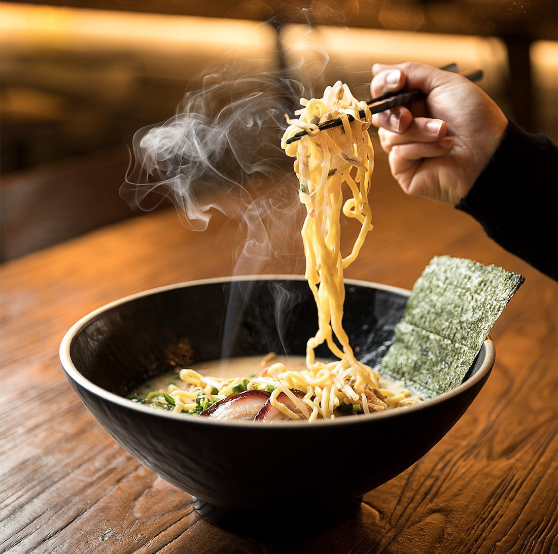 Hot bowl of ramen with chopsticks picking up noodles
