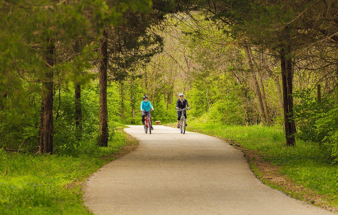 two people bike down trail