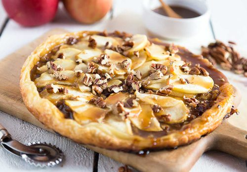 the circular pastry sits on a wooden serving platter, pecan scattered on top