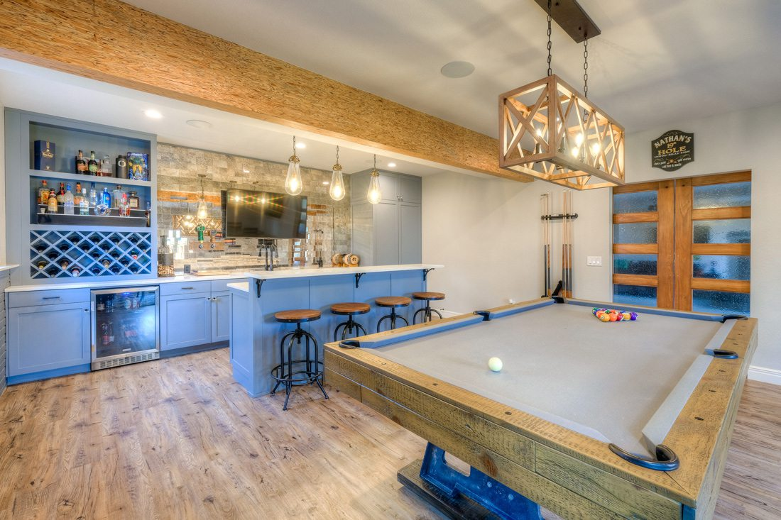 Basement bar with pool table and wine rack.