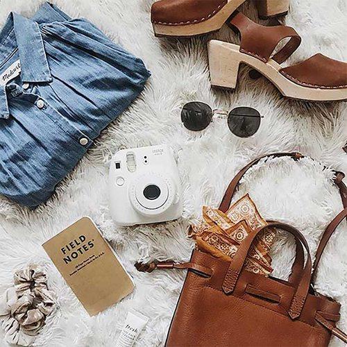 bag, camera, sunglasses, heeled shoes, jean shirt strewn across a shag, furry rug