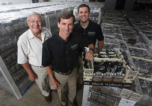 Dwain, Brian, and Jacob standing in front of their extensive store of black walnuts