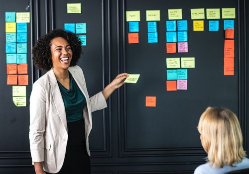 a business women uses sticky notes as a visual aid while leading a presentation