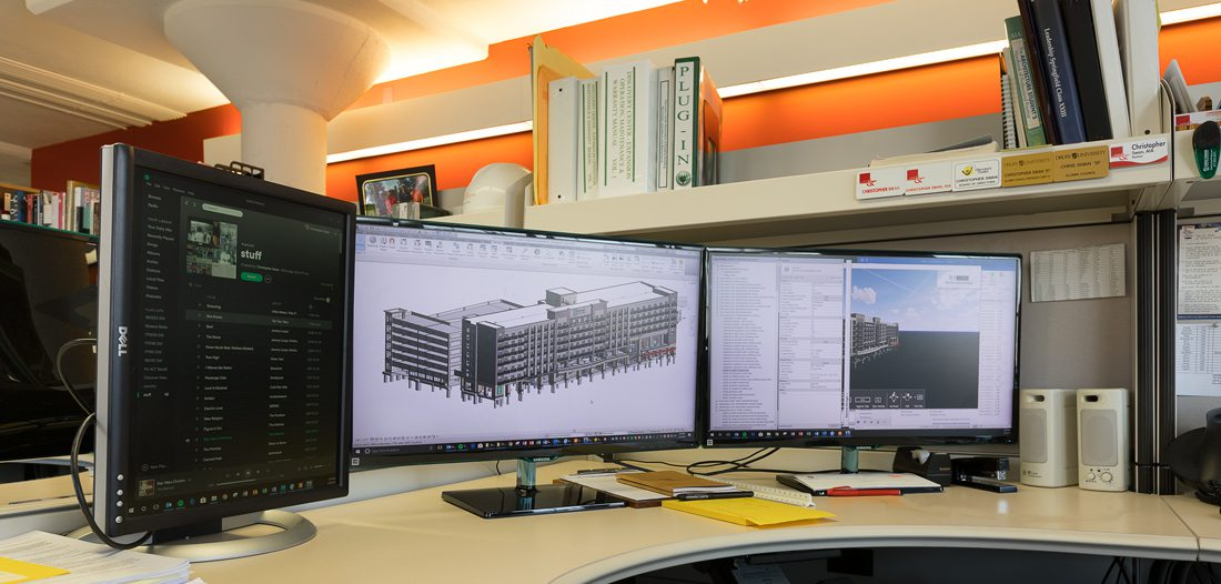 Computer screens in modern office with architecture plans.