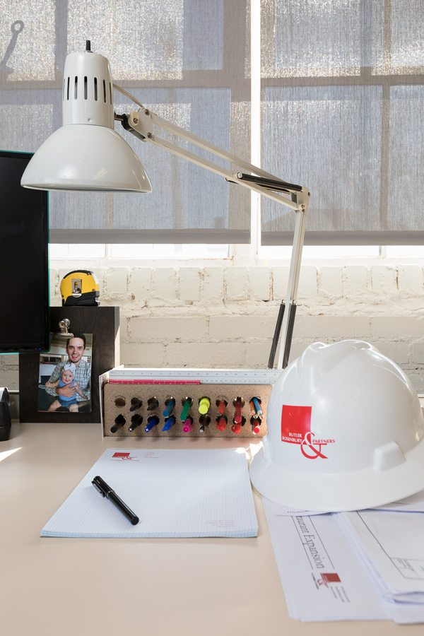 Hard hat on bright modern desk with lamp